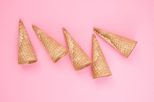 Rożki waflowe puste lodów na różowym tle Premium Zdjęcia