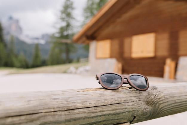 Rozmycie Zdjęcia Górskiego Drewnianego Domu W Lesie Z Modnymi Okularami Przeciwsłonecznymi Na Pierwszym Planie Darmowe Zdjęcia