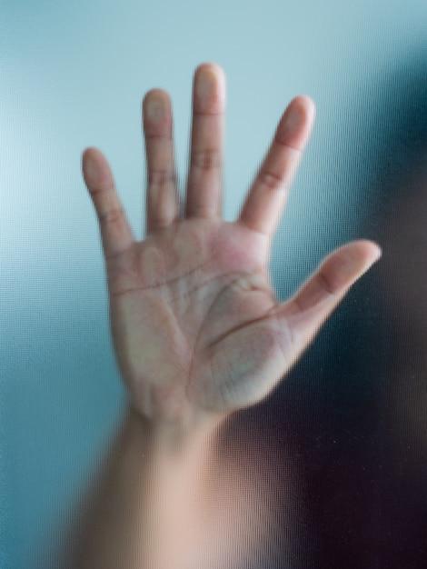 Rozmyty kobiety ręka za matową szklaną metaforą paniką i negatywnym zmrokiem emocjonalnym Premium Zdjęcia
