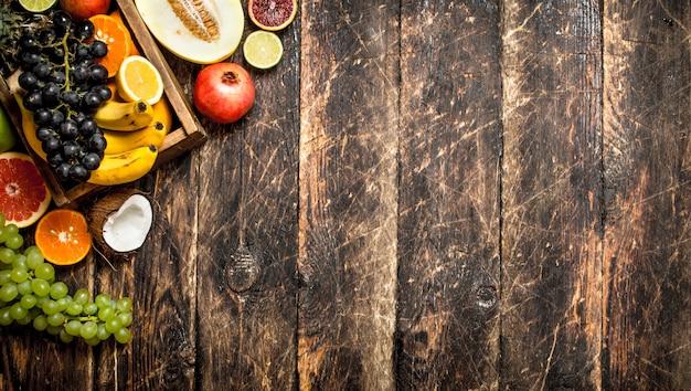 Różne Dojrzałe Owoce W Drewnianym Pudełku Na Drewnianym Stole. Premium Zdjęcia