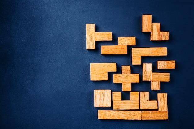 Różne geometryczne kształty drewniane klocki układają się w solidną figurę na ciemnym tle Premium Zdjęcia