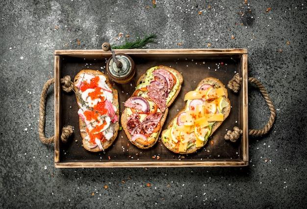 Różne Kanapki Z Owocami Morza, Mięsem I Warzywami Na Starej Tacy Na Rustykalnym Stole. Premium Zdjęcia
