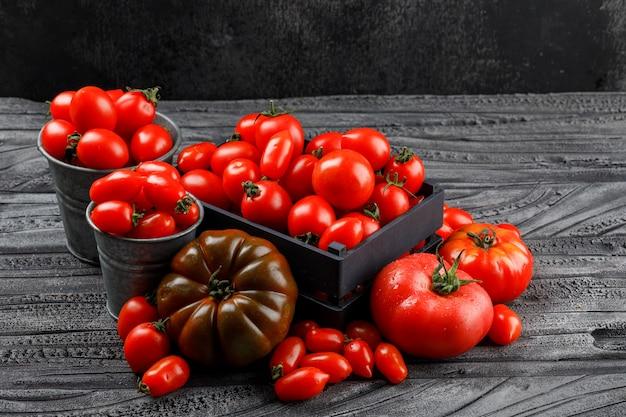 Różne Pomidory W Drewnianym Pudełku, Mini Wiadra Na Szarej Drewnianej I Ciemnej ścianie, Wysoki Kąt Widzenia. Darmowe Zdjęcia
