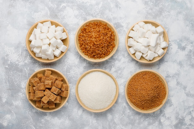 Różne rodzaje cukru, cukru brązowego i białego na betonie, widok z góry Darmowe Zdjęcia