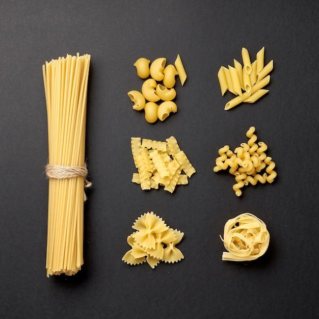 Różne rodzaje makaronów na czarnym tle Premium Zdjęcia