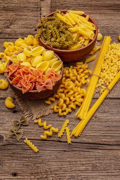 Różne Rodzaje Makaronów W Ceramicznych Misach. Tradycyjne Włoskie Jedzenie, Zdrowe Odżywianie. Rustykalny Drewniany Stół Premium Zdjęcia