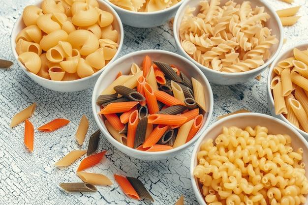 Różne rodzaje makaronów w miskach na stole. Premium Zdjęcia