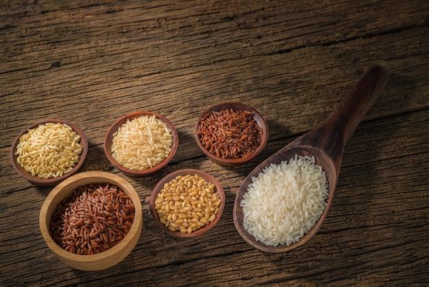 Różne Rodzaje Ziaren Zbóż (pszenica, Ryż, Ryż Brązowy, Kasza Gryczana, Jęczmień, Czarny Sezam, Proso, Nasiona Lotosu, łzy Hioba) Różne Surowe Surowe Ziarna Na Tle Drewna. Premium Zdjęcia