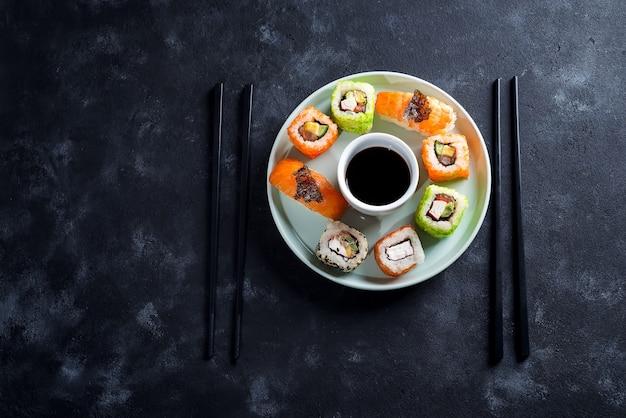 Różne Sushi świeże I Pyszne Na Płytce Ceramicznej Z łupków, Sos Na Czarnym Tle Kamienia Premium Zdjęcia