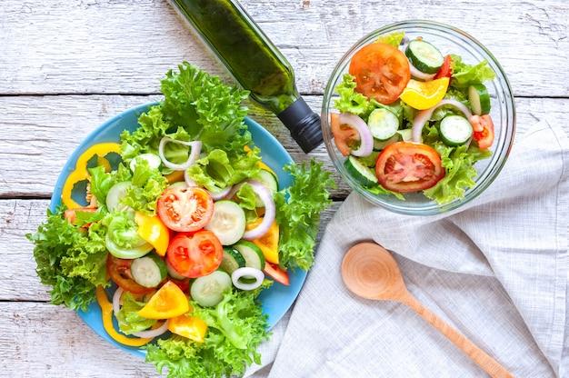 Różne świeże sałatki mix z pomidorami, ogórkiem, cebulą, papryką, zdrową żywnością i dietą m Premium Zdjęcia