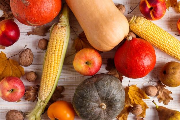 Różne warzywa dynie, jabłka, gruszki, orzechy, kukurydza, pomidory, suche żółte liście na białym tle drewnianych. jesienne żniwa, lato. Premium Zdjęcia