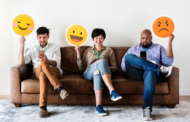 Różni ludzie siedzi i trzyma logo emoji Premium Zdjęcia