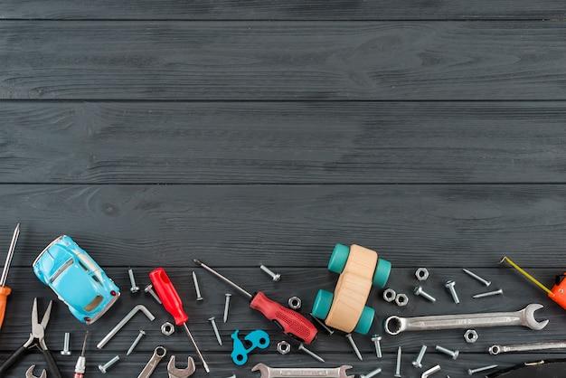 Różni narzędzia z zabawkarskim samochodem na czarnym stole Darmowe Zdjęcia