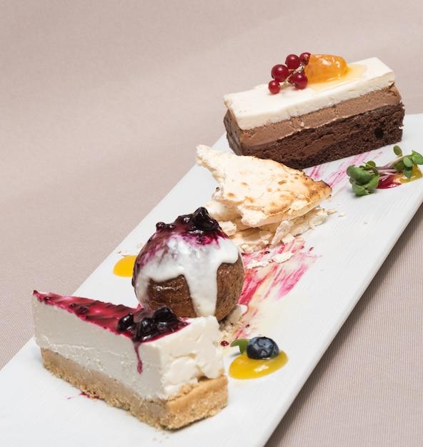 Różni typ deser umieszczający na bielu talerzu Premium Zdjęcia