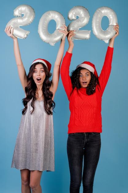 Różnorodne kobiety z 2020 nowymi balonami jest ubranym boże narodzenie kapelusze odizolowywających Premium Zdjęcia