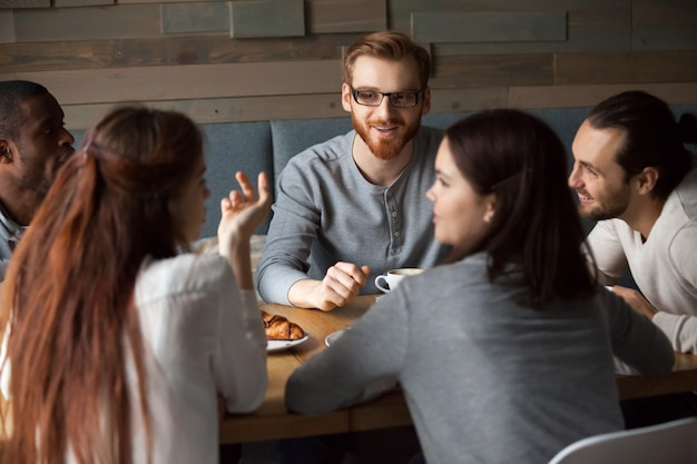 Różnorodni młodzi ludzie opowiada zabawę w kawiarni i ma wpólnie Darmowe Zdjęcia