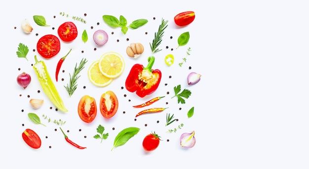 Różnorodni świezi warzywa i ziele dalej nad białym tłem. Premium Zdjęcia