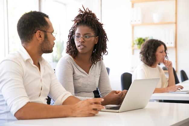 Różnorodni Ucznie Siedzi Przy Biurkiem Z Laptopem Darmowe Zdjęcia