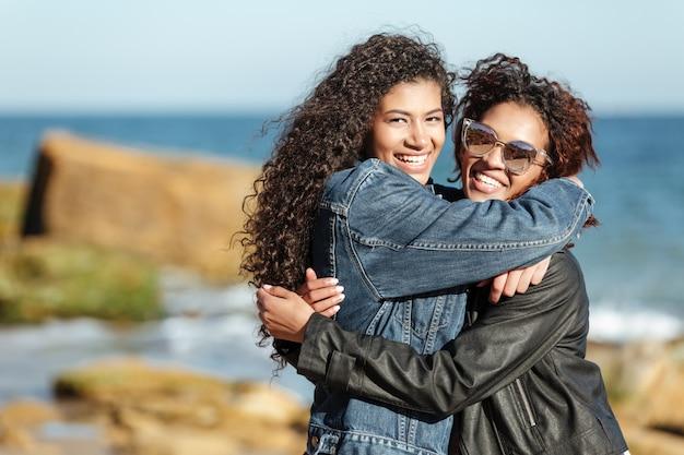 Rozochoceni Afrykańscy Kobieta Przyjaciele Chodzi Outdoors Przy Plażą. Darmowe Zdjęcia