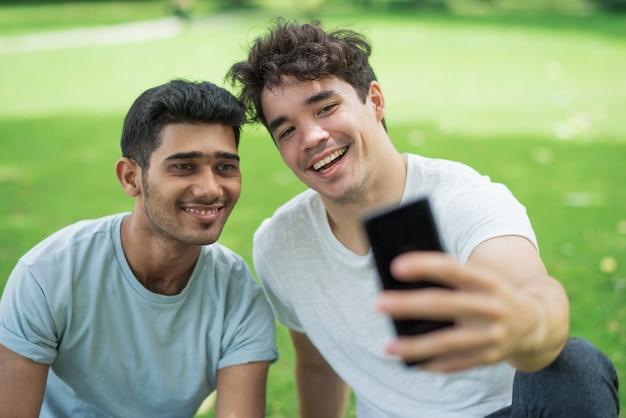 Rozochoceni beztroscy młodzi człowiecy bierze selfie na telefonie Darmowe Zdjęcia