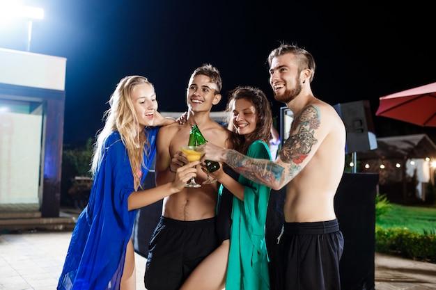 Rozochoceni Przyjaciele Uśmiecha Się, Raduje Się, Odpoczywa Przy Przyjęciem Blisko Pływackiego Basenu Darmowe Zdjęcia