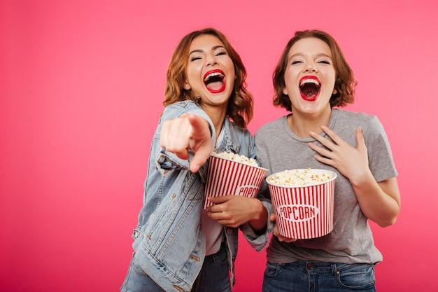 Rozochoceni Roześmiani Kobieta Przyjaciele Je Popkornu Zegarka Filmu Wskazywać. Darmowe Zdjęcia