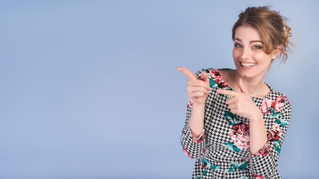 Rozochocona atrakcyjna kobieta wskazuje przy stroną w eleganckiej sukni Darmowe Zdjęcia