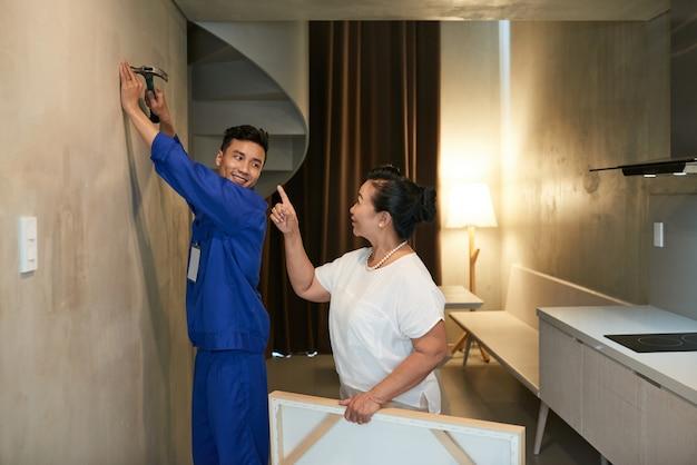 Rozochocona azjatycka złota rączka wbija gwóźdź i kobiety właściciel domu daje instrukcjom Darmowe Zdjęcia