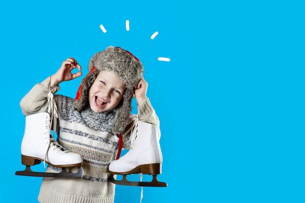 Rozochocona chłopiec trzyma lodowe łyżwy na błękitnym tle w kapeluszu z nausznikami Premium Zdjęcia