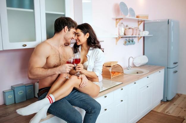Rozochocona I Szczęśliwa Potomstwo Para W Kuchni. Siedzą Na Szafce Kuchennej I Uśmiechają Się. Ludzie Mają W Rękach Kieliszki Czerwonego Wina. Premium Zdjęcia