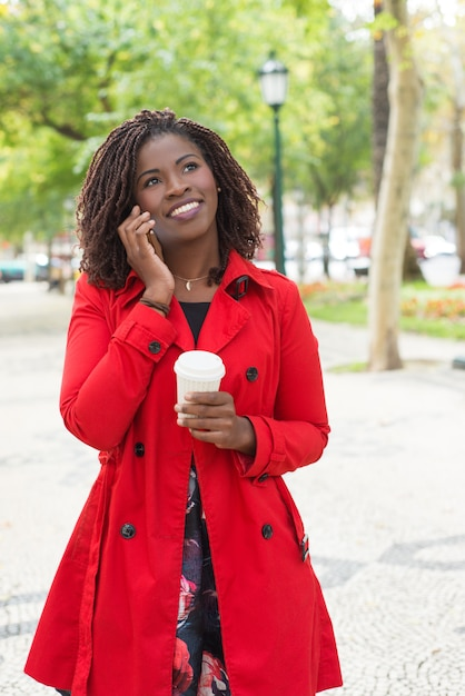 Rozochocona Kobieta Opowiada Smartphone Z Papierową Filiżanką Darmowe Zdjęcia