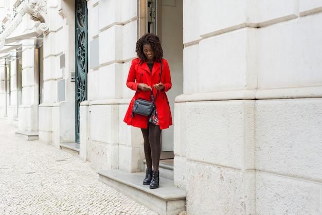 Rozochocona Kobieta Stoi Blisko Budynku Z Smartphone Darmowe Zdjęcia