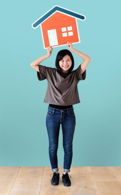 Rozochocona kobieta trzyma domową ikonę Darmowe Zdjęcia