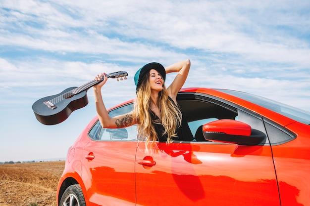 Rozochocona kobieta z ukulele w samochodzie Darmowe Zdjęcia