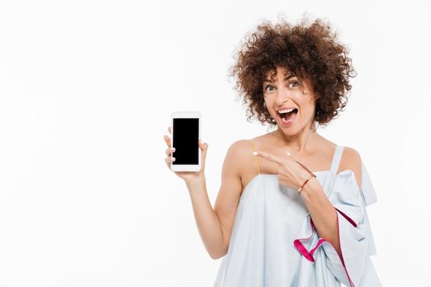 Rozochocona ładna Kobieta Wskazuje Palec Przy Pustego Ekranu Telefonem Komórkowym Darmowe Zdjęcia