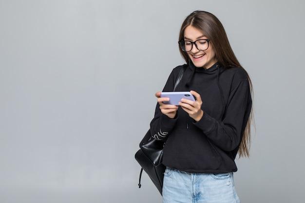 Rozochocona Młoda Dziewczyna Z Plecak Sztuki Grze Z Telefonem Komórkowym Odizolowywającym Na Biel ścianie. Darmowe Zdjęcia