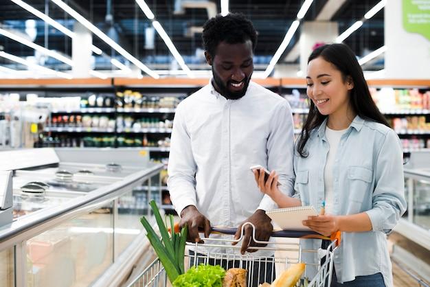 Rozochocona Para Sprawdza Na Mobilnej Liście Zakupów Przy Supermarketem Z Wózek Na Zakupy Darmowe Zdjęcia