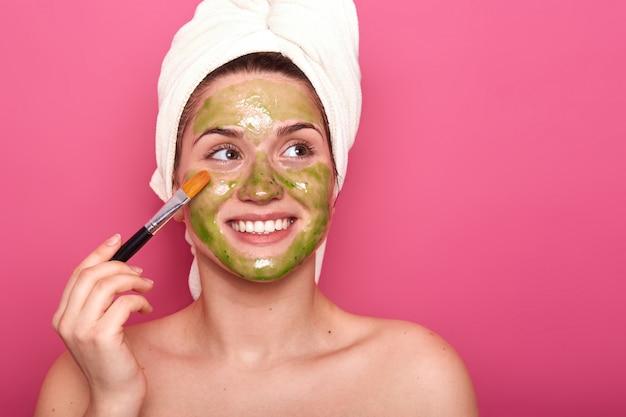 Rozochocona Pozytywna Młoda Kobieta Stawia Kolorową Maskę Na Jej Twarzy Z Pomocą Profesjonalisty Muśnięcia, Patrzeje Na Boku, Jest Szczęśliwy. Atrakcyjna Dziewczyna Lubi Spędzać Czas Na Zabiegach Pielęgnacyjnych Skóry. Darmowe Zdjęcia