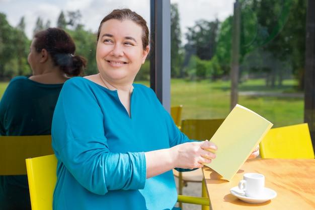 Rozochocona w średnim wieku dama wydaje jej ranek w sklep z kawą Darmowe Zdjęcia