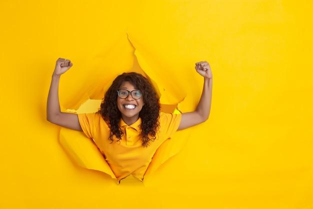 Rozochocone Młodych Kobiet Pozy W Poszarpanym Koloru żółtego Papieru Dziury Tle, Emocjonalny I Ekspresyjny Darmowe Zdjęcia