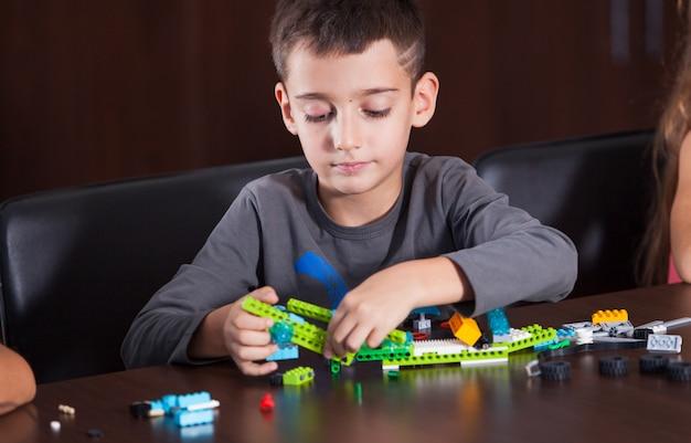 Rozochocone Uśmiechnięte Dzieci Budują Konstruktora. Premium Zdjęcia