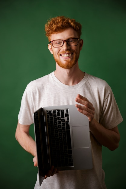 Rozochoconego Readhead Brodaty Mężczyzna W Szkłach I Białym Tshirt Trzyma Laptop W Rękach Darmowe Zdjęcia