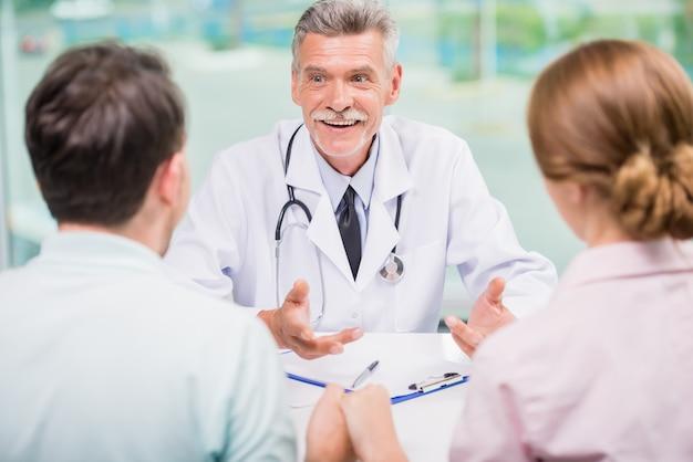 Rozochocony Doktorski Opowiadać Z Rodzinną Parą Przy Kliniką. Premium Zdjęcia