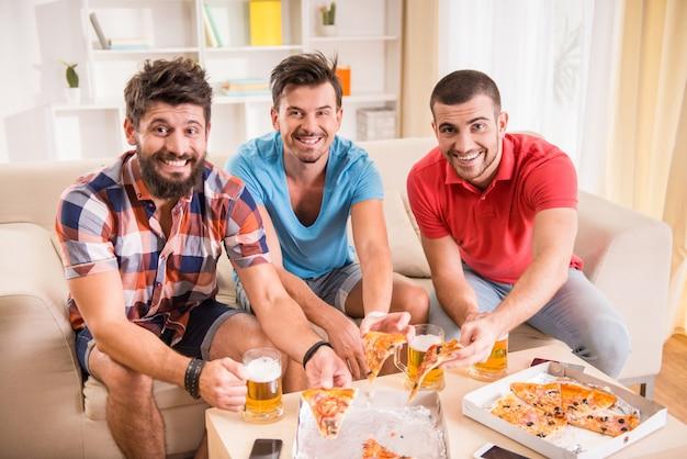 Rozochocony mężczyzna ogląda futbol w domu i je. Premium Zdjęcia