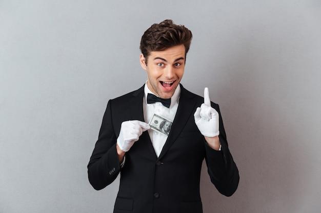 Rozochocony Młody Kelner Trzyma Pieniądze Pomysłu Wskazywać. Darmowe Zdjęcia