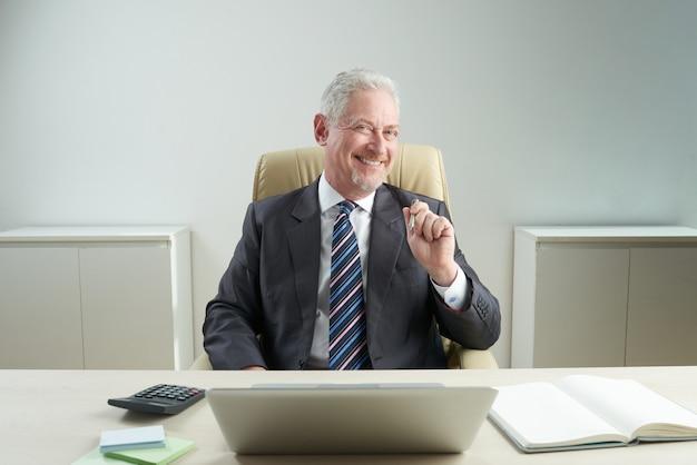 Rozochocony starszy biznesmen pozuje dla fotografii Darmowe Zdjęcia