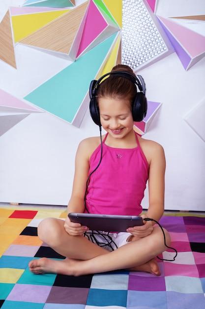 Rozochocony szczęśliwy dziecko słucha film z hełmofonami Premium Zdjęcia