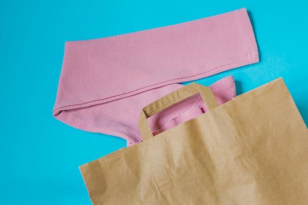 Różowa bluzka kobiety w paczce papieru na niebiesko. Premium Zdjęcia