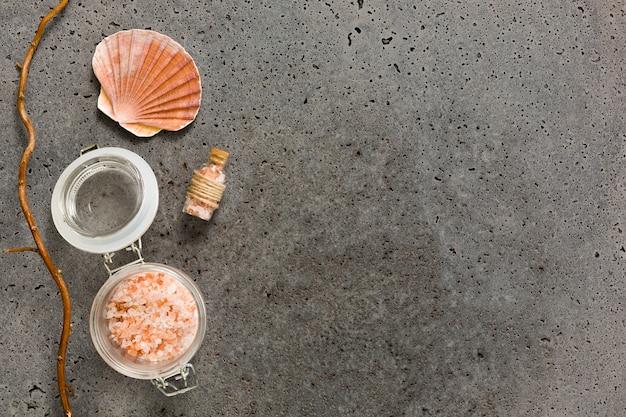 Różowa Kąpielowa Sól W Zbiorniku Z Seashell Na Betonie Textured Darmowe Zdjęcia
