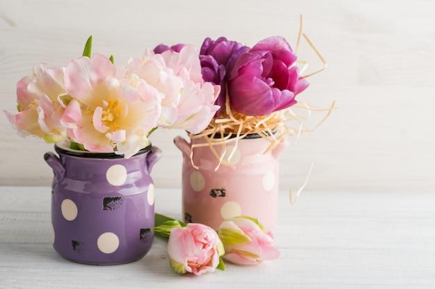 Różowe i fioletowe tulipany w uroczych glinianych doniczkach Premium Zdjęcia